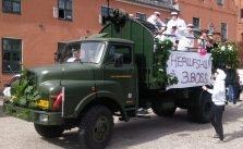 grøn studentervogn med studenter i hvide trøjer