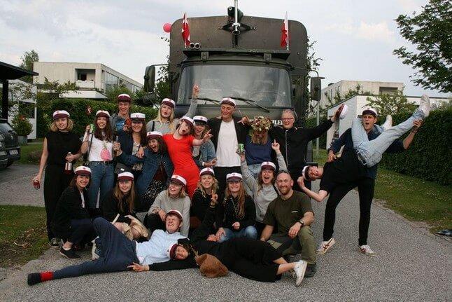 En gymnasieklasse som fejrer med studenterkørsel foran en studentervogn